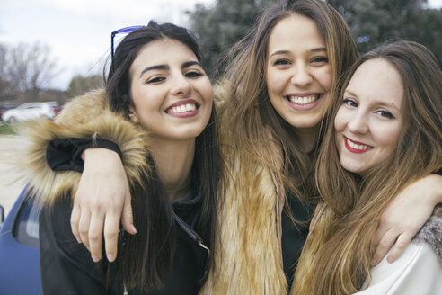 Group picture of three happy young women arm in arm - ABZF000340