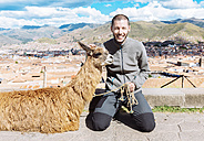Peru, Cusco, portrait of happy tourist kneeling beside llama - GEMF000844