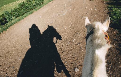 Peru, Cusco, shadow of woman riding horse on dirt road - GEMF000853