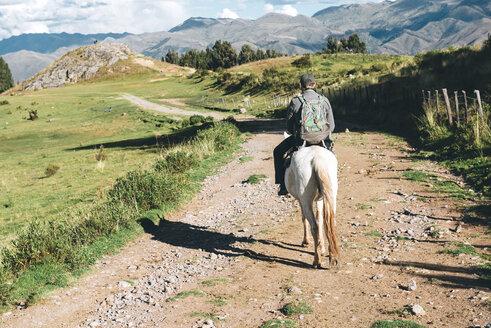 Peru, Cusco, back view of man riding horse - GEMF000856