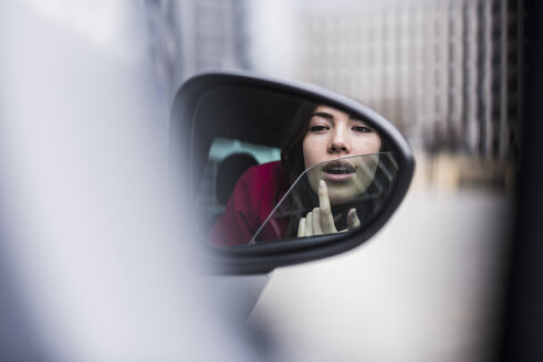 Pretty woman sitting in car applying make up in wing mirror - UUF006859