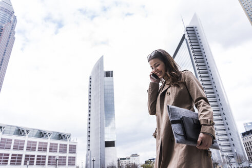 Young businesswoman walking in city using mobile phone - UUF006880