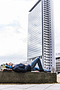 Young businessman lying on wall listening music with headphones - UUF006886