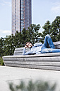 Young man lying on bench using digital tablet - UUF006916