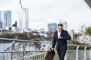 Young businessman walking in the city, checking time - UUF006934