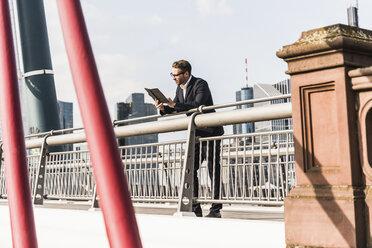 Young businessman using digital tablet standing on bridge - UUF006943