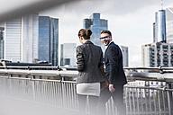 Young business couple walking on bridge, talking - UUF006946