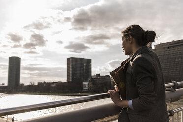 Germany, Frankfurt, Young woman looking at river - UUF006949