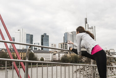 Young woman jogging in the city, stretching leg - UUF006961