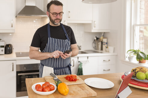 Portrait of man using smartphone while preparing food in the kitchen - BOYF000253