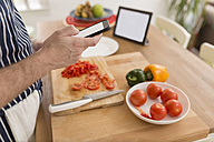 Man using smartphone while preparing food in the kitchen, close-up - BOYF000256