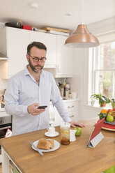 Man standing in his kitchen in the morning looking at his smartphone - BOYF000265