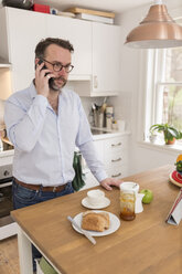 Man standing at breakfast table in the kitchen telephoning with smartphone - BOYF000268