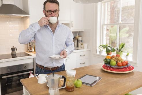 Man standing in his kitchen having breakfast - BOYF000277