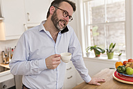Man standing in the kitchen with cup  telephoning with smartphone - BOYF000280