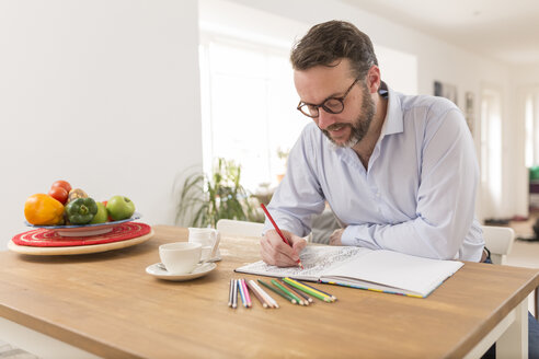 Man with colouring book and coloured pencils sitting at wooden table - BOYF000283