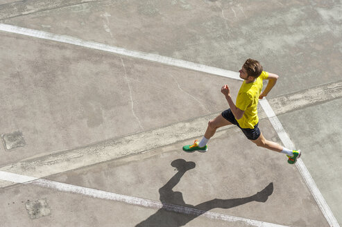 Young man jogging, concrete floor - DIGF000248