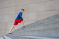 Young jogger stretching on steps - DIGF000260