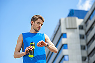 Young sporty man with water bottle and smartwatch - DIGF000263