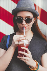 Portrait of young woman wearing hat and sunglasses drinking soft drink - RTBF000117