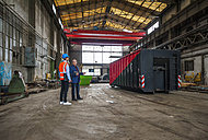 Manager and worker talking at container in factory hall - DIGF000266