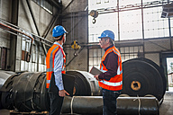 Two men with safety vests in factory hall with rolls of rubber - DIGF000272