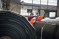 Two men with safety vests in factory hall with rolls of rubber - DIGF000275