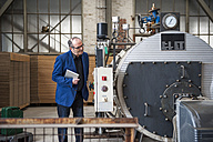 Manager in factory hall looking at machine - DIGF000281