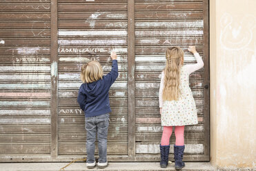 Back view of two little girls drawing on an old garage door - DRF001709