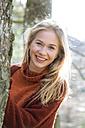 Portrait of happy teenage girl besides tree trunk - WWF003944