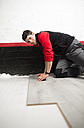 Young man placing a laminate floor - RAEF001053