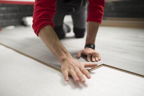 Young man placing a laminate floor - RAEF001056