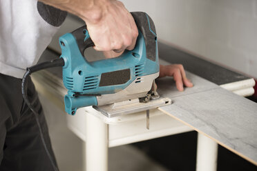 Man cutting laminate floor pieces with a jigsaw - RAEF001062