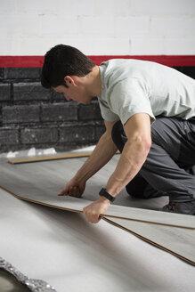 Young man placing a laminate floor - RAEF001065