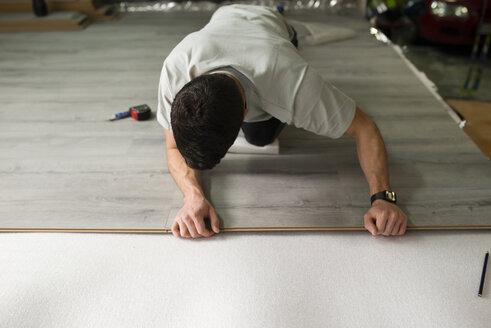 Young man placing a laminate floor - RAEF001068