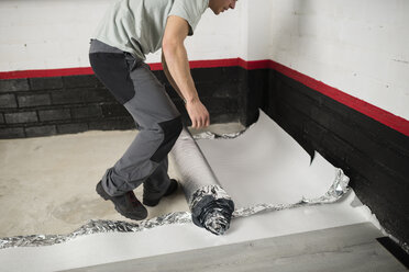Young man placing a insulating material for a laminate flooring - RAEF001071