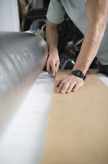 Young man cutting a insulating material for a laminate flooring - RAEF001074