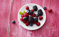 Dish of different wild berries on pink wood - KSWF001758