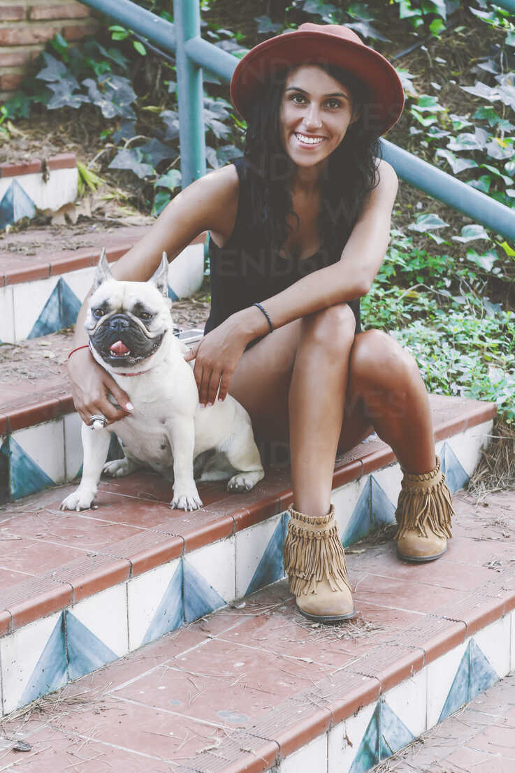 Portrait of smiling woman sitting with her dog on stairs - RTBF000131 - Retales Botijero/Westend61
