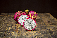 Sliced and whole dragon fruits on dark wood - LVF004751