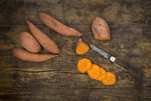 Sliced and whole sweet potatoes on dark wood - LVF004757