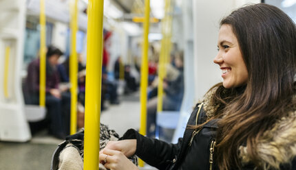 UK, London, happy young woman in an underground train - MGOF001726