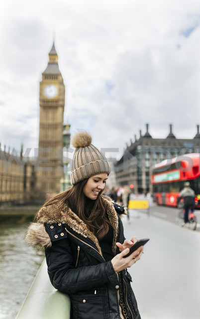 UK, London, smiling young woman looking at her smartphone in front of Palace of Westminster - MGOF001729