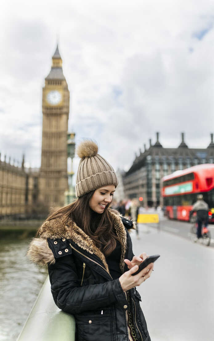 UK, London, smiling young woman looking at her smartphone in front of Palace of Westminster - MGOF001729 - Marco Govel/Westend61