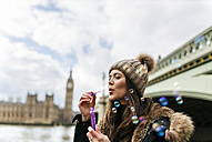 UK, London, young woman blowing soap bubbles - MGOF001732