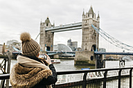 UK, London, back view of young woman taking picture of Tower of London - MGOF001735
