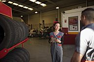 Mechanic checking tires and wheels in workshop - JASF000666