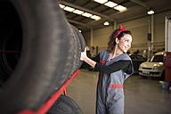 Woman taking tire in workshop - JASF000678