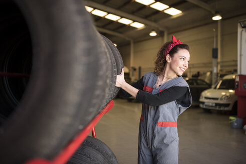Woman taking tire in workshop - JASF000678