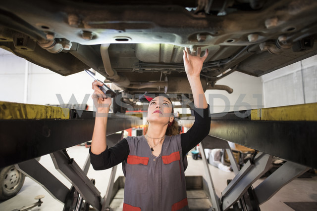 Mechanic woman working under a car with led light - JASF000681 - Jaen Stock/Westend61
